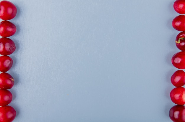 Zakończenie widok czerwone wiśnie po lewej i prawej stronie na błękit powierzchni z kopii przestrzenią
