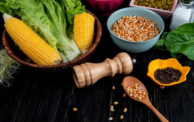 Zakończenie widok gotująca kukurudzy ziarna kukurydzy sałata z solankową łyżką czarnego pieprzu szpinakiem na czerni powierzchni