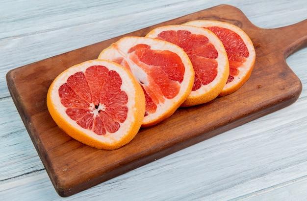 Zakończenie widok grapefruitowi plasterki na tnącej desce na drewnianym tle