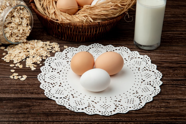 Zakończenie widok jajka na papierowej doily powierzchni z płatków owsianych i mlekiem na drewnianym tle