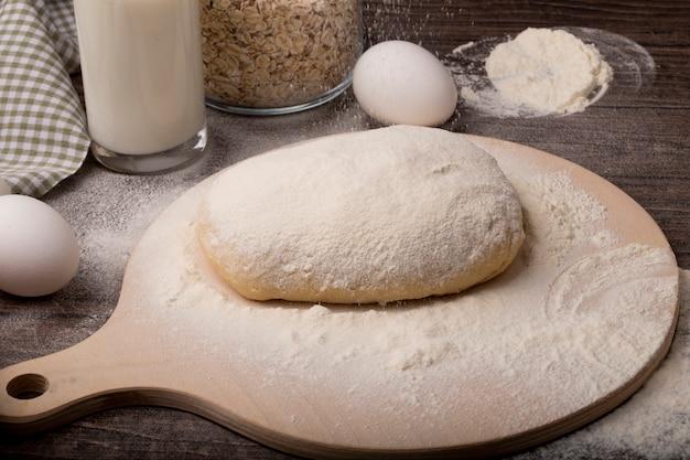 Zakończenie widok kropiący z mąką ciasto na tnącej desce z jajkami na drewnianym tle ciasto