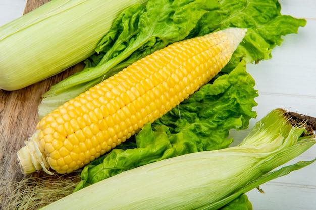Zakończenie widok kukurydzani cobs i sałata na drewnianym stole