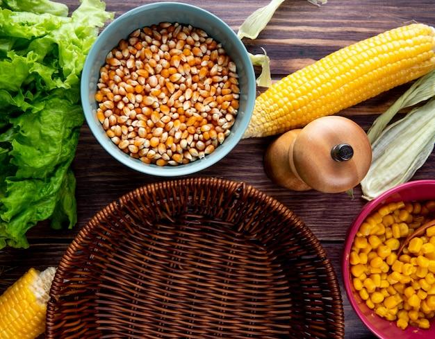 Zakończenie widok kukurydzani ziarna z sałatkami kukurudze i pusty kosz na drewnianym stole