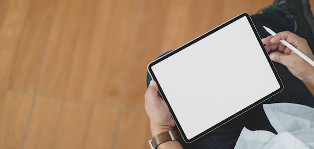 Zakończenie widok mężczyzna używa pustego ekranu cyfrową pastylkę podczas gdy siedzący w jego biurowym pokoju