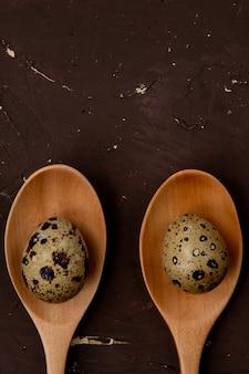 Zakończenie widok mini jajka na drewnianych łyżkach na brown tle z kopii przestrzenią