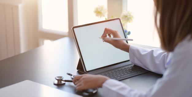 Zakończenie widok młodej kobiety lekarka pisze medycznych mapach z pastylką w biurowym pokoju