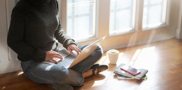 Zakończenie widok młody żeński freelancer pracuje nad jej projektem z laptopem