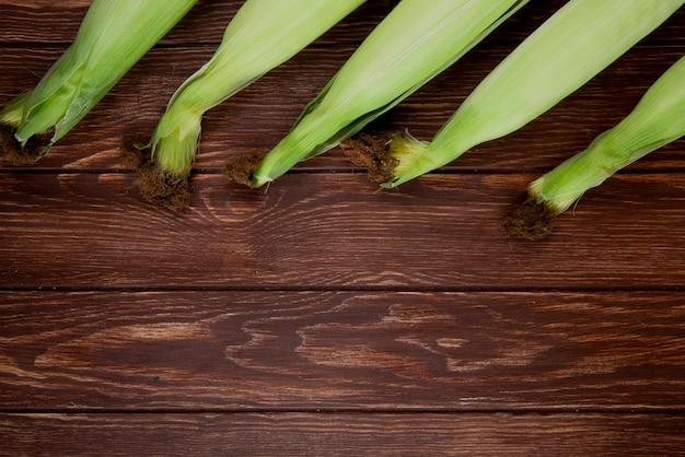 Zakończenie widok niegotowane kukurudze na drewnianej powierzchni z kopii przestrzenią