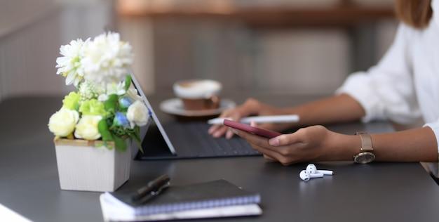 Zakończenie widok pisać na maszynie na cyfrowej pastylce młody bizneswoman podczas gdy używać smartphone