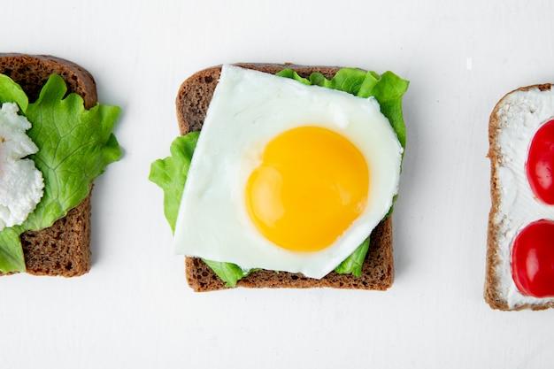Zakończenie widok plasterek chleb z jajecznym yolk holland serem i szpinakiem na nim na bielu