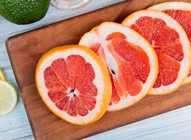 Zakończenie widok pokrojony grapefruitowy na tnącej desce na drewnianym tle