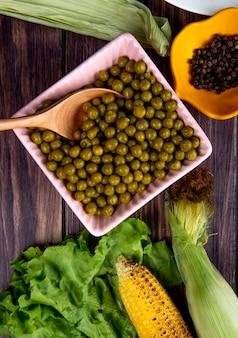 Zakończenie widok puchar zielony groszek z sałaty kukurudze i czarny pieprz na drewnianej powierzchni