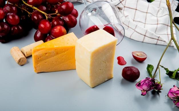Zakończenie widok ser i szkło czerwone wino i winogrono z korkami i kwiatami na bielu