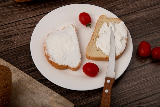 Zakończenie widok talerz białego chleba plasterki mazał z twarogu, pomidory i nóż na drewnianym tle