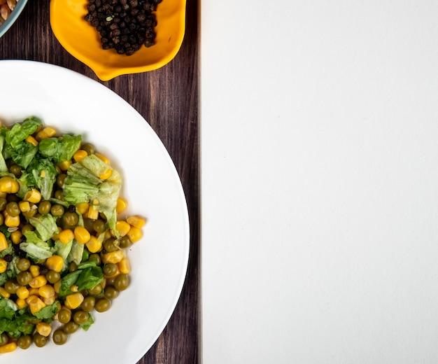Zakończenie widok talerz kukurydzana sałatka z czarnego pieprzu ziarnami na drewnianej powierzchni z kopii przestrzenią