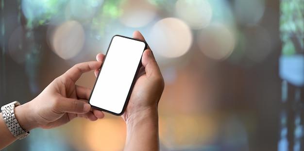 Zakończenie widok trzyma pustego ekranu smartphone z bokeh tłem mężczyzna