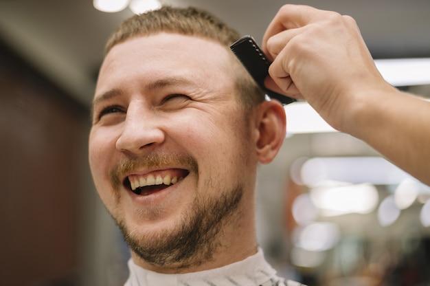Zakończenie widok uśmiechnięty mężczyzna przy fryzjera męskiego sklepem