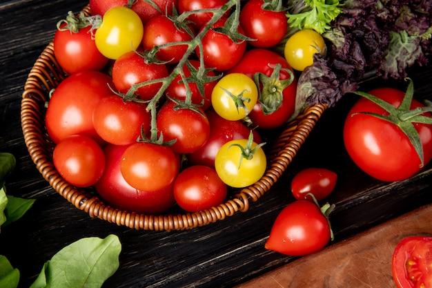 Zakończenie widok warzywa jako pomidorowa basil kolendra w koszu z szpinakiem na drewnianym stole