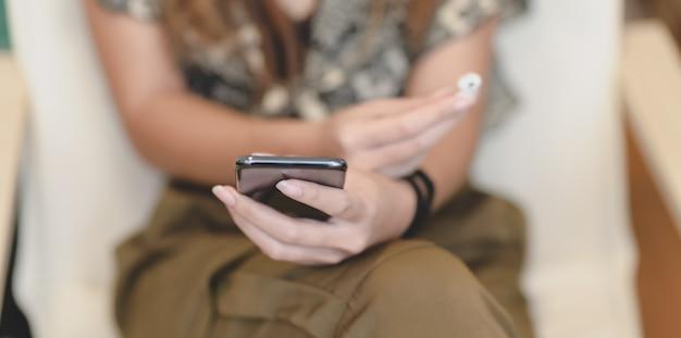 Zakończenie widok żeński mienia smartphone i słuchawka