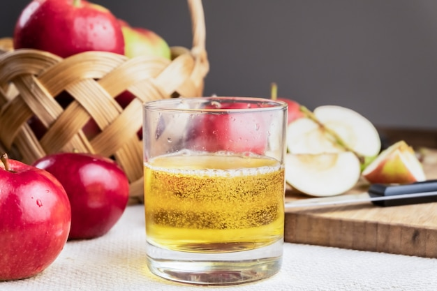 Zakończenie wizerunek cidre napój i dojrzali soczyści jabłka na nieociosanym drewnianym stole. szklanka domowego cydru i lokalnie uprawianych jabłek ekologicznych