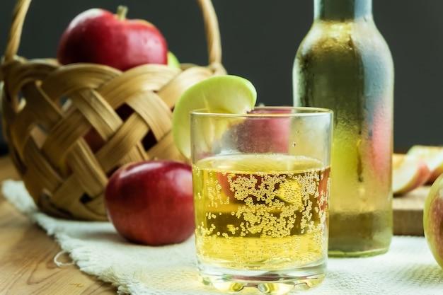 Zakończenie wizerunek iskrzasty cidre napój i dojrzali soczyści jabłka na nieociosanym drewnianym stole. szklanka domowego cydru i lokalnie uprawianych jabłek ekologicznych