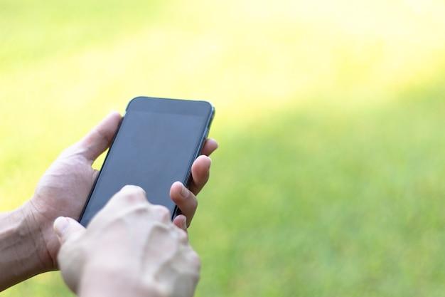 Zakończenie wizerunku samiec wręcza używać czarnego smartphone w parku