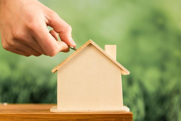 Zakończenie wkłada monetę w drewnianym domu na drewnianym stole ręka