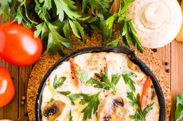 Zakończenie włoski frittata, pomidory, pieczarki i pietruszka na drewnianym stole. widok z góry