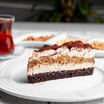 Zakończenie wyśmienicie deser w talerzu z herbatą, dokrętki na białym drewnianym tle.