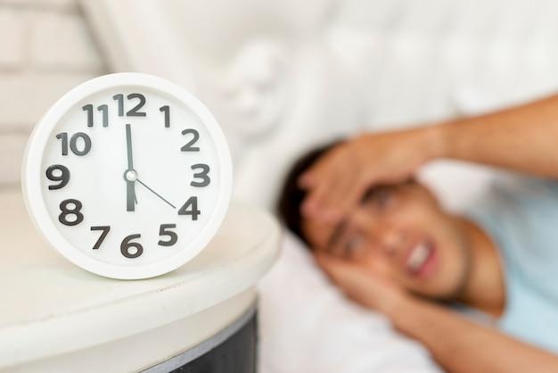 Zakończenie zamazany śpiący facet z zegarem