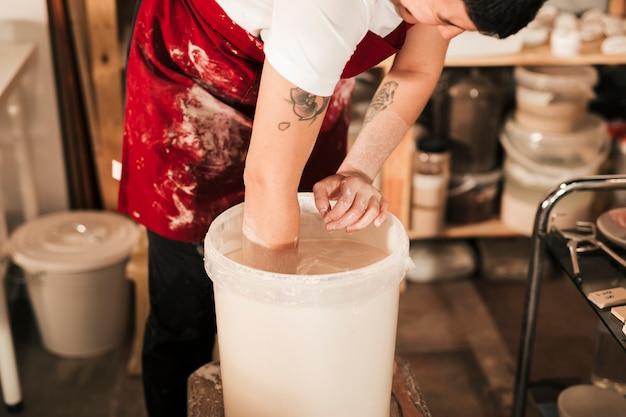 Zakończenie żeńska garncarka przygotowywa farbę w wiadrze
