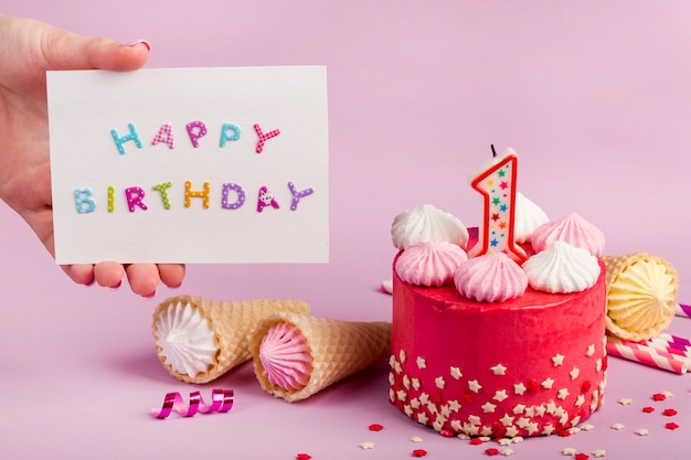 Zakończenie żeńska ręka trzyma wszystkiego najlepszego z okazji urodzin kartę blisko dekoracyjnego torta przeciw purpurowemu tłu