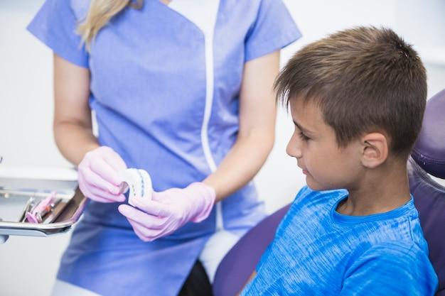 Zakończenie żeński dentysta pokazuje zęby tynk foremkę pacjent w klinice