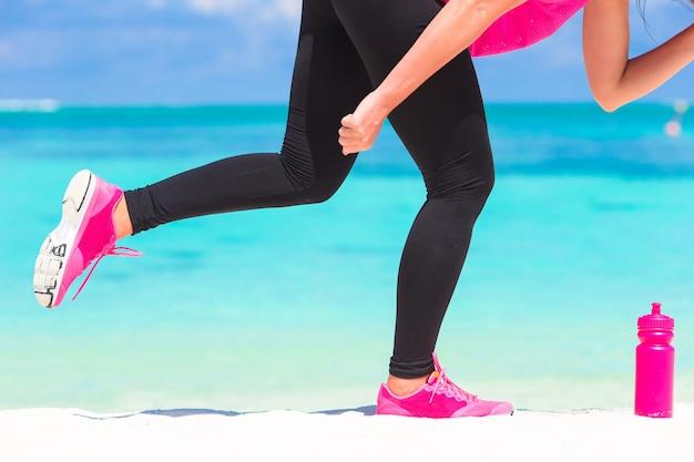 Zakończenie żeńskie nogi w sneakers biega na białej piaskowatej plaży