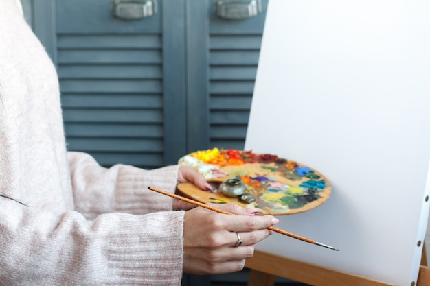 Zakończenie żeńskie ręki w różowym pulowerze trzyma muśnięcie i paletę