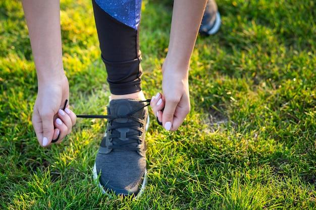 Zakończenie żeńskie ręki wiąże shoelace na butach do biegania przed praktyką. biegacz przygotowuje się do treningu. koncepcja aktywnego stylu życia sportowego.