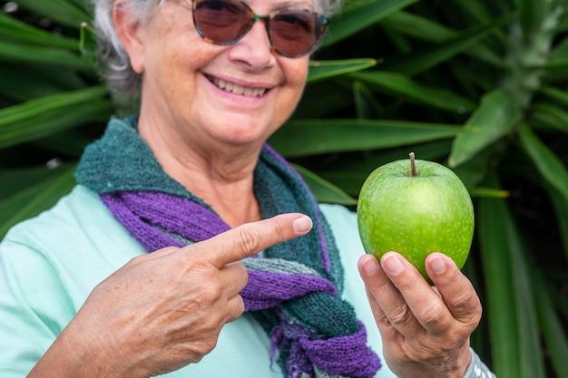 Zakończenie zielone jabłko trzyma starsza uśmiechnięta kobieta. pojęcie zdrowego odżywiania i diety