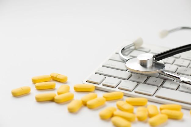 Zakończenie żółte pigułki i stetoskop na klawiaturze nad białym tłem
