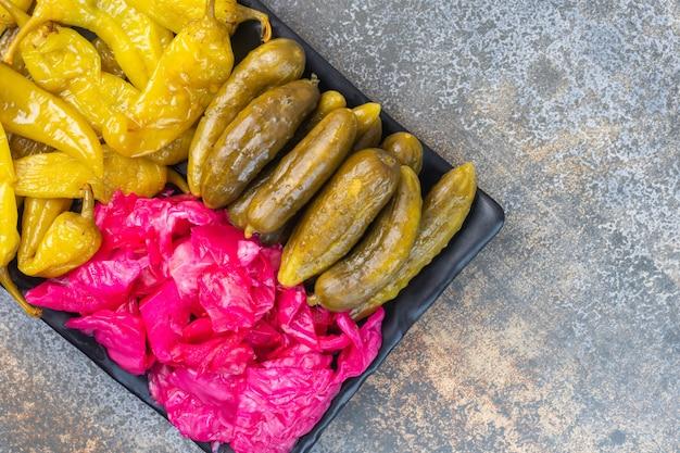 Zakonserwowane ostre papryczki, ogórki i kapusta kiszona na półmisku