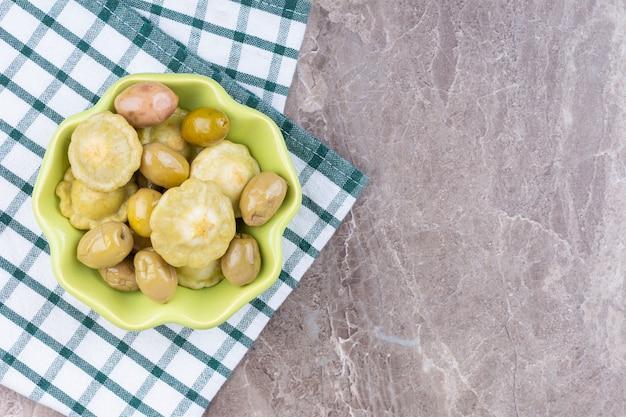 Zakonserwowany pattypan squash i oliwka w misce na ręczniku, na marmurze.