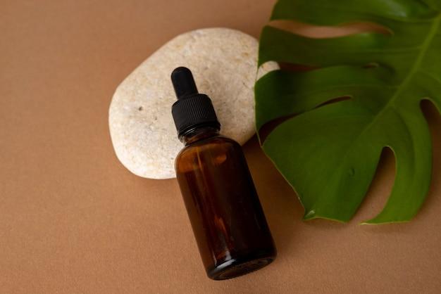 Zakraplacz z brązowego szkła z olejkiem kosmetycznym z rośliną monstera i kamieniem na tle terakoty, zbliżenie.
