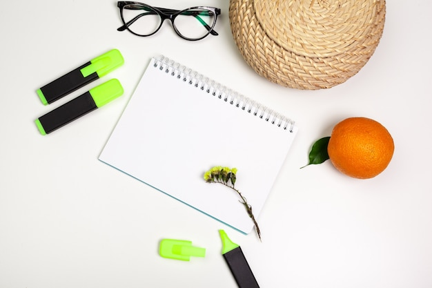 Zakreślacze i pusty arkusz papieru do notatnika leżały płasko na biurku