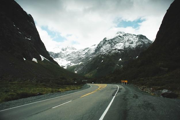 Zakręt drogi na wsi z ośnieżonymi górami i pięknymi chmurami na niebie