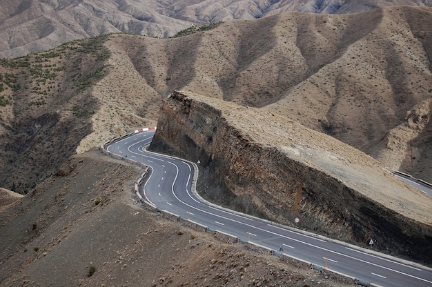 Zakręt drogi wokół klifu z górami