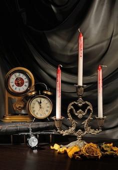 Zakrwawione świece na stole z zegarem i zwiędłymi różami