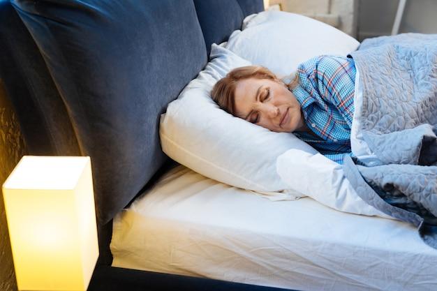 Zakryte i ciepłe. dorosła jasnowłosa kobieta leżąca z zamkniętymi oczami przykryta ciepłym kocem w jasnej piżamie