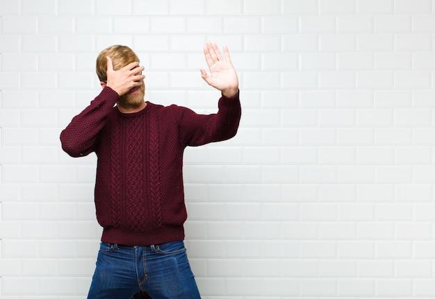 Zakrywając twarz dłonią i kładąc drugą rękę z przodu, aby się zatrzymać