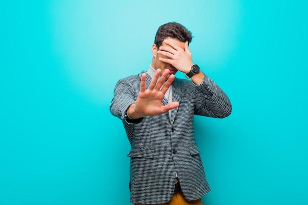 Zakrywając twarz dłonią i kładąc drugą rękę z przodu, aby zatrzymać aparat, odmawiając zdjęć lub zdjęć