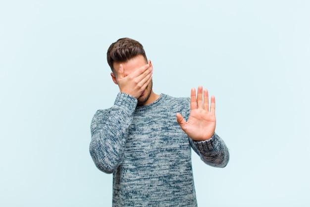 Zakrywając twarz dłonią i kładąc drugą rękę z przodu, aby zatrzymać, odmawiając zdjęć lub zdjęć