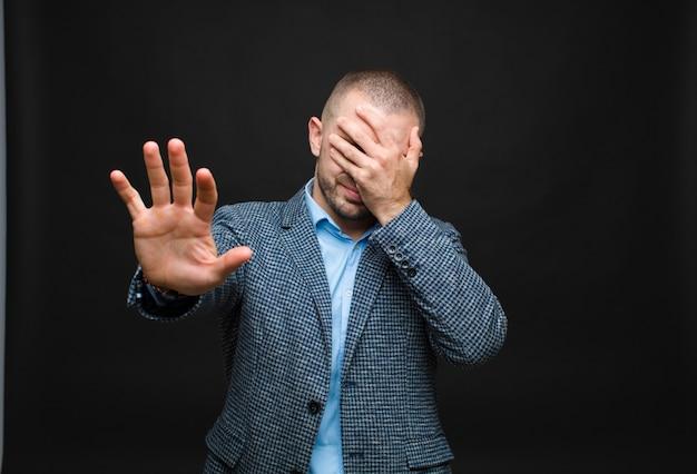 Zakrywanie twarzy ręką i zatrzymanie drugiej ręki do góry, odmawianie zdjęć lub obrazków